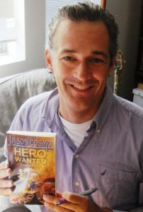 Author Dan McGirt holds a copy of his book Hero Wanted